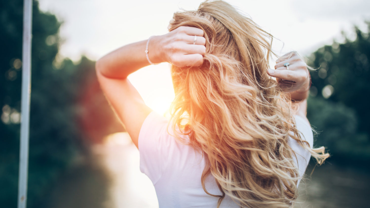 Woman facing into sun holding her wavy hair