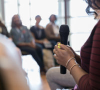 Woman holding microphone speaking to a group - Webinar