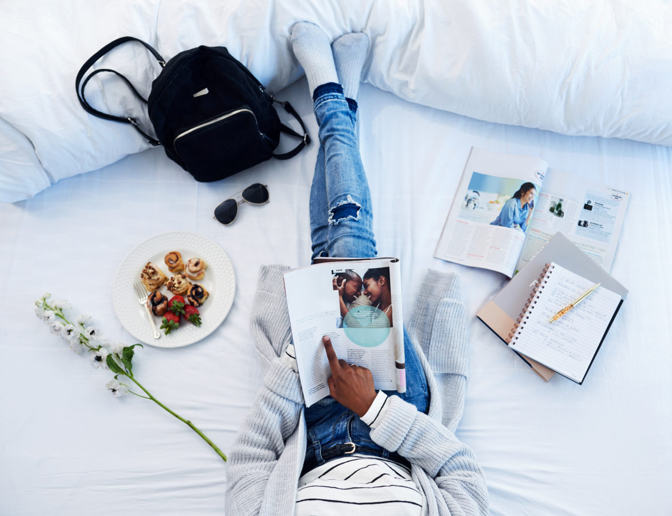 Above view of a person sitting on a bed reading a magazine with notes and desserts nearby